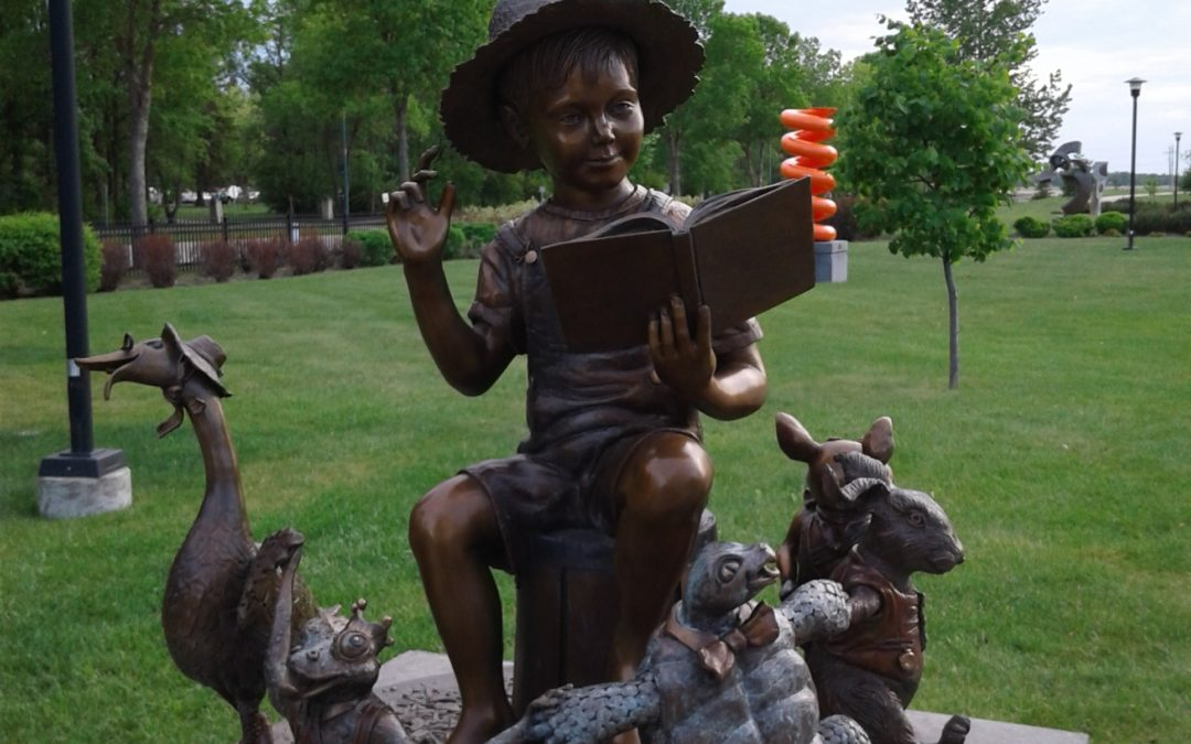 Sculpture of boy reading to story book characters.