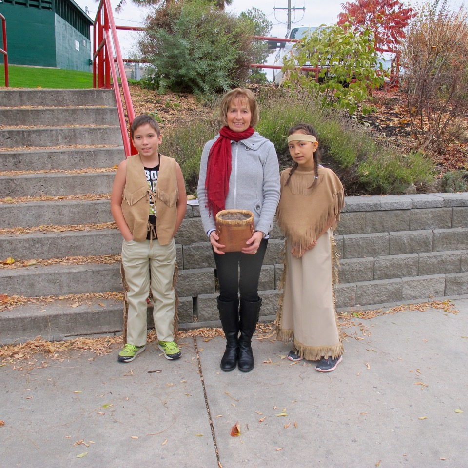 Two children in First Nations garb with a woman in western garb.